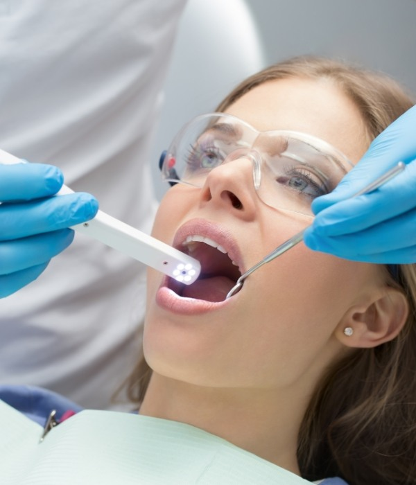 Dentist performing oral cancer screening