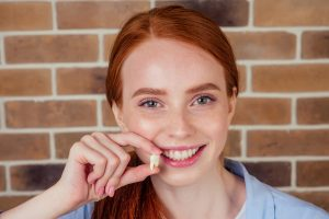Young woman holding extracted wisdom tooth and smiling