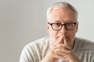 Man in glasses thinking with fingers crossed on his mouth
